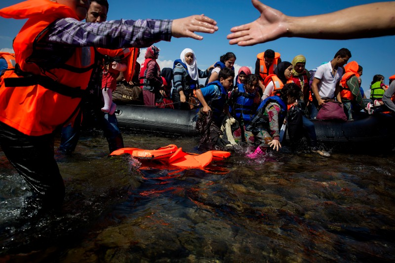 LESBOS, GREECE - SEPTEMBER 08:  Refugees come ashore near the village of Skala Sikamineas on September 8, 2015 in Lesbos, Greece. More than 230,000 people have landed on Greek shores this year, pushing the island of Lesbos to it's limits. (Photo by Eric Thayer/Getty Images)