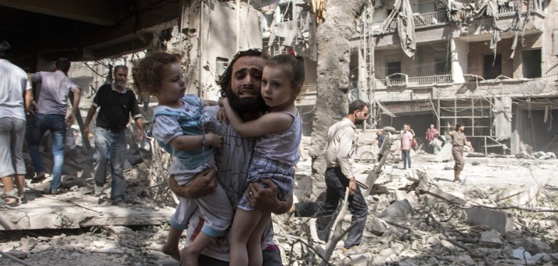 A Syrian man carries his two girls as he walks across the rubble following a barrel bomb attack on the rebel-held neighbourhood of al-Kalasa in the northern Syrian city of Aleppo on September 17, 2015. Once Syria's economic powerhouse, Aleppo has been ravaged by fighting since the rebels seized the east of the city in 2012, confining government forces to the west. AFP PHOTO / KARAM AL-MASRI        (Photo credit should read KARAM AL-MASRI/AFP/Getty Images)