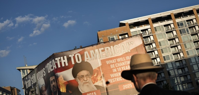 A man walks past a billboard lobbying against an agreement with Iran over its nuclear program September 17, 2015 in Washington, DC.  Iran's foreign minister said last week that Washington must honour a nuclear deal between Tehran and major powers once implementation begins and block any attempt by lawmakers to meddle with it. AFP PHOTO/BRENDAN SMIALOWSKI        (Photo credit should read BRENDAN SMIALOWSKI/AFP/Getty Images)