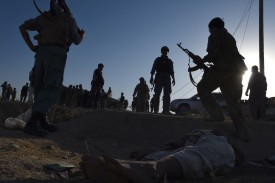 Afghan security forces stand over a body of a Taliban militant after fighting between Taliban militants and Afghan security forces near the airport in Kunduz on October 1, 2015. Afghan forces pushed into the centre of Kunduz on October 1, triggering pitched gunfights as they sought to flush out Taliban insurgents who held the northern city for three days in a stinging blow to the country's NATO-trained military The stunning fall of the provincial capital, even temporarily, highlighted the stubborn insurgency's potential to expand beyond its rural strongholds in the south of the country Afghan forces, hindered by the slow arrival of reinforcements but backed by NATO special forces and US air support, struggled to regain control of the city after three days of heavy fighting. AFP PHOTO / Wakil Kohsar        (Photo credit should read WAKIL KOHSAR/AFP/Getty Images)