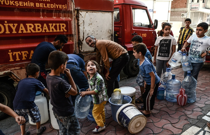 People collect water from a fire vehicle parked along a street of Silvan on October 5, 2015, clashes between the Turkish army and Kurdish rebels. Turkish authorities imposed a curfew in the mainly Kurdish southeastern town of Silvan, saying 17 suspected Kurdish militants had already been killed hours after the military lockdown was enforced. AFP PHOTO / ILYAS AKENGIN        (Photo credit should read ILYAS AKENGIN/AFP/Getty Images)