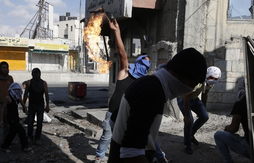 A masked Palestinian youth throws a petrol bomb towards Israeli security forces during clashes at the Qalandia checkpoint between Jerusalem and Ramallah, in the Israeli-occupied West Bank, on October 6, 2015. Palestinian president Mahmud Abbas said he wanted to avoid a violent escalation with Israel, his most direct comments since unrest has spread in recent days and provoked fears of a new uprising. His comments came as Prime Minister Benjamin Netanyahu pledged a crackdown and Israel, in a show of force, demolished the homes of two Palestinians who carried out attacks last year.   AFP PHOTO / ABBAS MOMANI        (Photo credit should read ABBAS MOMANI/AFP/Getty Images)
