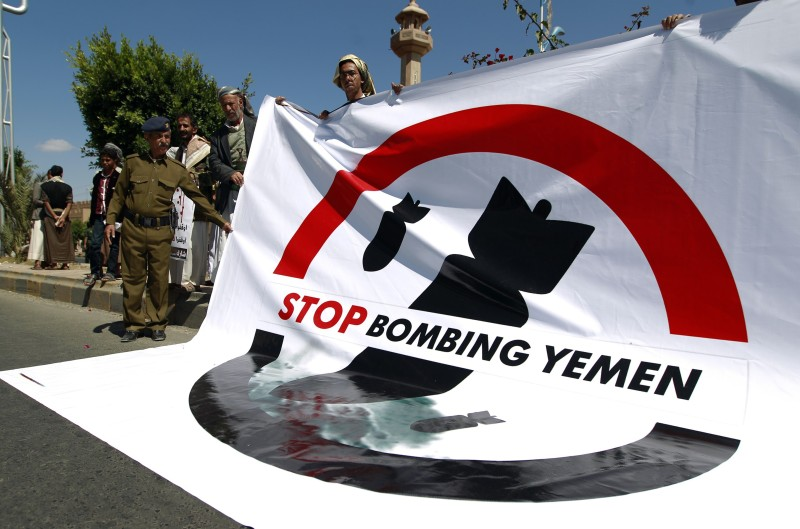 Yemeni demonstrators hold a huge poster bearing a slogan, against ongoing military operations and airstrikes carried out by the Saudi-led coalition on Yemen, during a protest in front of the United Nations (UN) office in the capital Sanaa on October 18, 2015, .  AFP PHOTO / MOHAMMED HUWAIS        (Photo credit should read MOHAMMED HUWAIS/AFP/Getty Images)