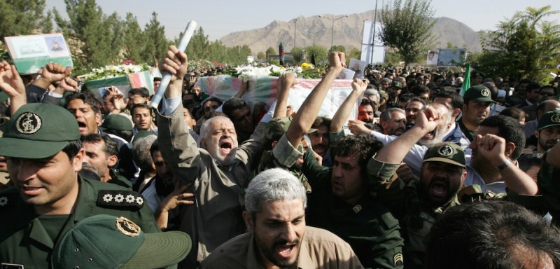 Iranians carry the coffin of General Nur-Ali Shushtari, deputy commander of the Revolutionary Guards ground forces and other members of the Revolutionary guardians, killed two days ago, near the Pakistani border, during a funeral in Tehran outside the Revolutionary Guard garrison on October 20, 2009. Sunni group Jundallah claimed responsibility for the suicide attack that killed seven Revolutionary Guards commanders and 28 other people, including several tribal leaders. AFP PHOTO AFP PHOTO/BEHROUZ MEHRI (Photo credit should read )