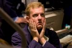 A trader rubs his face on the floor of the New York Stock Exchange in New York on Oct. 3, 2008. (Jeremy Bales/Bloomberg via Getty Images)