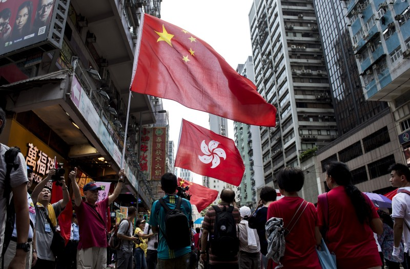 People hold the Chinese and Hong Kong flags as they take part in a pro-government rally in Hong Kong on August 17, 2014.  Thousands protested in Hong Kong on August 17 against plans by pro-democracy activists to paralyse the city centre with a mass sit-in unless China grants acceptable electoral reforms.      AFP PHOTO / ALEX OGLE        (Photo credit should read Alex Ogle/AFP/Getty Images)