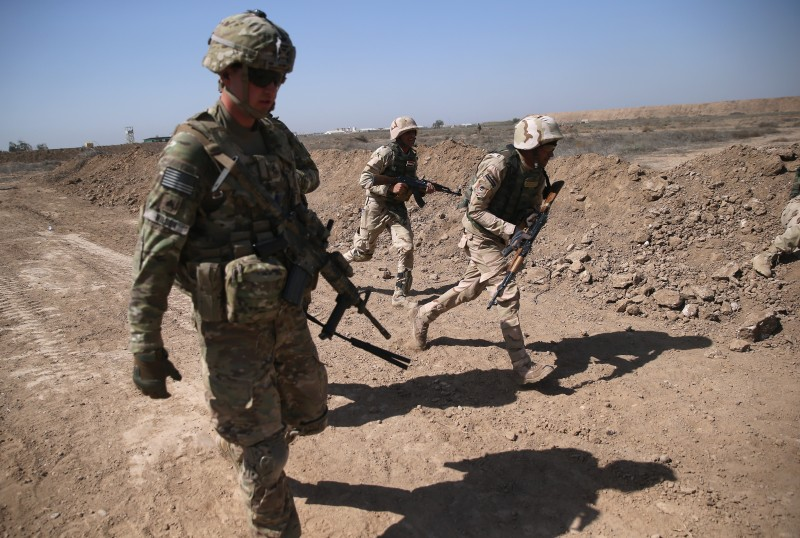TAJI, IRAQ - APRIL 12:  A U.S. Army trainer (L), instructs Iraqi Army recruits at a military base on April 12, 2015 in Taji, Iraq. U.S. forces, currently operating in 5 large bases throught Iraq, are training thousands of Iraqi Army combat troops, trying to rebuild a force they had origninally trained before the U.S. withdrawal from Iraq in 2010. Members of the U.S. Army's 5-73 CAV, 3BCT, 82nd Airborne Division are teaching members of the newly-formed 15th Division of the Iraqi Army, as the Iraqi government launches offensives to try to recover territory lost to ISIS last year.  (Photo by John Moore/Getty Images)
