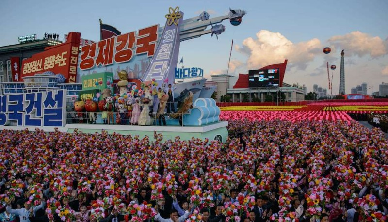 Participants wave flowers during a mass military parade in Pyongyang on October 10, 2015. North Korea was marking the 70th anniversary of its ruling Workers' Party. AFP PHOTO / Ed Jones        (Photo credit should read ED JONES/AFP/Getty Images)