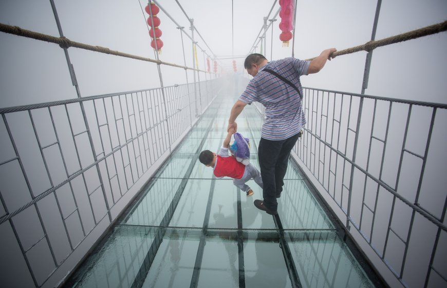 A Chinese tourist holds onto his son as they walk across a glass-bottomed suspension bridge in the Shiniuzhai mountains in Pingjiang county, Hunan province some 150 kilometers from Changsha on October 7, 2015.  The bridge, originally a wooden walkway spanning some 300 meters across the 180-meter deep valley, reopened two weeks ago following renovations as a glass-bottomed tourist attraction.   AFP PHOTO / JOHANNES EISELE        (Photo credit should read JOHANNES EISELE/AFP/Getty Images)