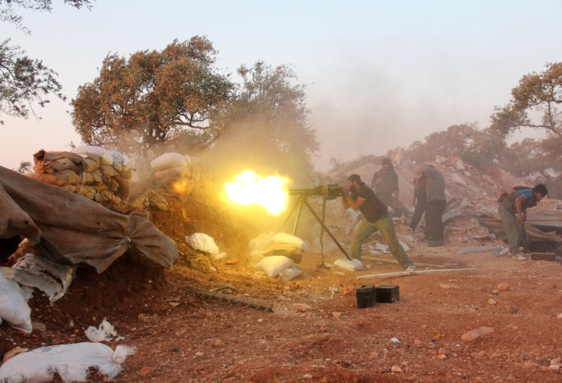 A rebel fighter fires a heavy machine gun during clashes with government forces and pro-regime shabiha militiamen in the outskirts of Syria's northwestern Idlib province on September 18, 2015. AFP PHOTO / OMAR HAJ KADHOUR        (Photo credit should read OMAR HAJ KADOUR/AFP/Getty Images)