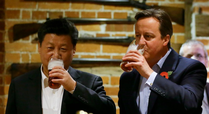 PRINCES RISBOROUGH, ENGLAND - OCTOBER 22: China's President Xi Jinping and Britain's Prime Minister David Cameron drink a pint of beer during a visit to the The Plough pub on October 22, 2015 in Princes Risborough, England. The President of the People's Republic of China, Mr Xi Jinping and his wife, Madame Peng Liyuan, are paying a State Visit to the United Kingdom as guests of The Queen.  They will stay at Buckingham Palace and undertake engagements in London and Manchester. The last state visit paid by a Chinese President to the UK was Hu Jintao in 2005.  (Photo by Kirsty Wigglesworth - WPA Pool/Getty Images)