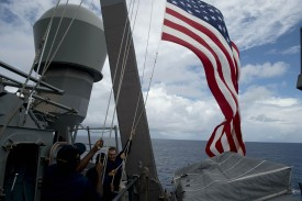 US Navy personnel raise their flag during the bilateral maritime exercise between the Philippine Navy and US Navy dubbed Cooperation Afloat Readiness and Training (CARAT 2014) aboard the USS John S. McCain in the South China Sea near waters claimed by Beijing on June 28, 2014.  The United States and the Philippines kicked off joint naval exercises in the South China Sea near waters claimed by Beijing, amid tense territorial rows between China and its neighbours. AFP PHOTO/NOEL CELIS/POOL        (Photo credit should read NOEL CELIS/AFP/Getty Images)
