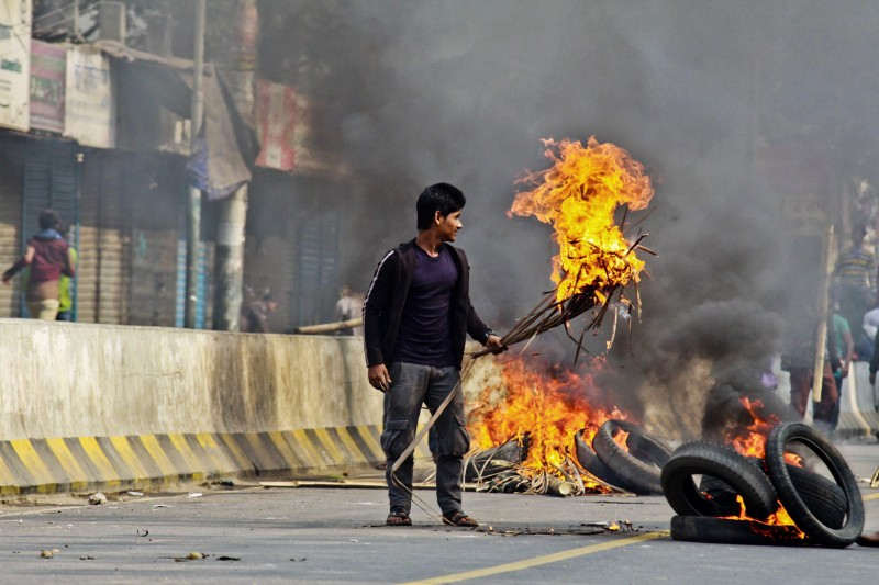 Bangladesh Nationalist Party (BNP) supporters set fire to tyres and material in the street during a clash with police outside a court in Dhaka on December 24, 2014, during a court appearance by party chief Khaleda Zia.  Zia and three of her aides are accused of syphoning off 31.5 million taka (about USD400,000) from a charitable trust named after her late husband Ziaur Rahman, a former president who was assassinated in 1981.  AFP PHOTO/STR        (Photo credit should read STRDEL/AFP/Getty Images)