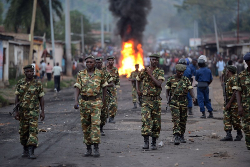 Burundian soldiers walk near a burning barricade erected by protesters as people demonstrate against the president's bid for a third term in power in Musaga, in the outskirts of Bujumbura, on April 27, 2015. Police in Burundi battled protestors on April 27 in a second day of demonstrations over a bid by the central African nation's president for a third term in office. AFP PHOTO / SIMON MAINA        (Photo credit should read SIMON MAINA/AFP/Getty Images)