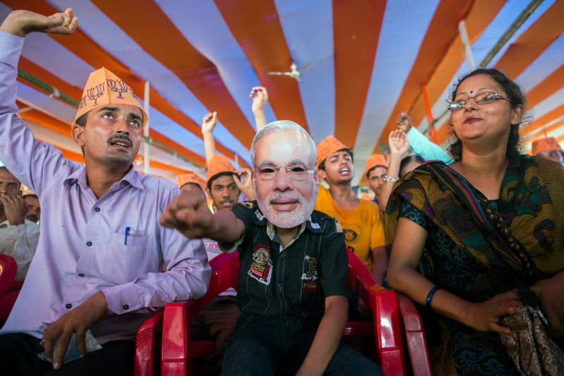 A supporter of the Bharatiya Janata Party (BJP) wears a mask of Indian Prime Minister Narendra Modi during a rally in Muzaffarpur, Bihar, India, on Saturday, July 25, 2015. More than anywhere, Bihar reflects the challenge Prime Minister Narendra Modi faces in overhauling modern India. A vast, landlocked plain bordering the Himalayan nation of Nepal to the north and bisected by the Ganges, India's holiest river, the state is home to about one in 12 Indians. Photographer: Prashanth Vishwanathan/Bloomberg via Getty Images