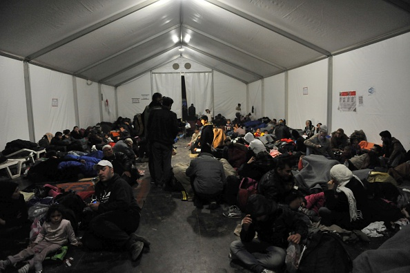 Migrants and refugees sitting in a tent of a camp station wait to cross the Greece-Macedonia (also referred as Former Yugoslavia  Rebublic of Makedonia) border, near the village of Idomeni on November 19, 2015. Countries along the migrant route through the Balkans have begun tightening restrictions on the wave  people crossing their borders by allowing entry only to those fleeing war, aid workers and officials said on November 19. AFP PHOTO / SAKIS MITROLIDIS        (Photo credit should read SAKIS MITROLIDIS/AFP/Getty Images)