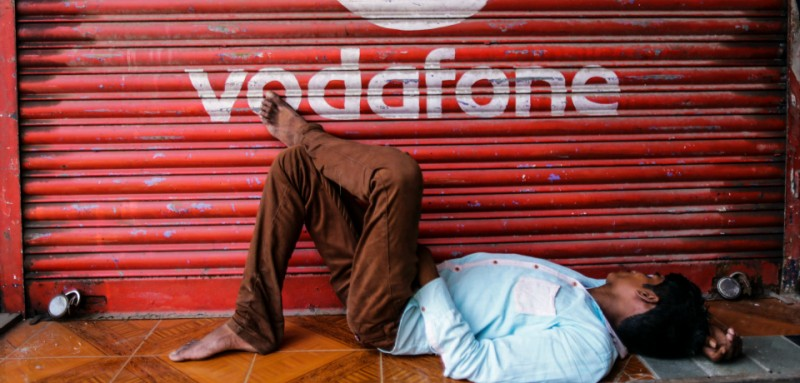 Vodafone india Ltd. logo sits on a a shop as a man takes nap in Mumbai, India, on Monday, Oct. 19, 2015. Photographer: Dhiraj Singh/Bloomberg
