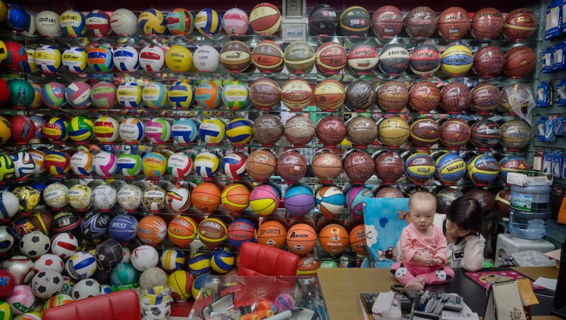 YIWU , CHINA - SEPTEMBER 25: A Chinese trader plays with her child as she waits for customers at her stall selling wholesale sports balls at the Yiwu International Trade City on September 25, 2015 in Yiwu, China. Considered the largest small commodity market in the world, the 46 million square foot facility houses more than 60 thousand vendors and 100,000 suppliers selling 400,000 products.  Two-thirds of the goods are for export from factories across China to over 200 countries, mainly Russia, the Middle East, Africa and South America.  A slowdown among China's manufacturers has triggered global concern of a drop in economic growth in the world's second largest economy. (Photo by Kevin Frayer/Getty Images)