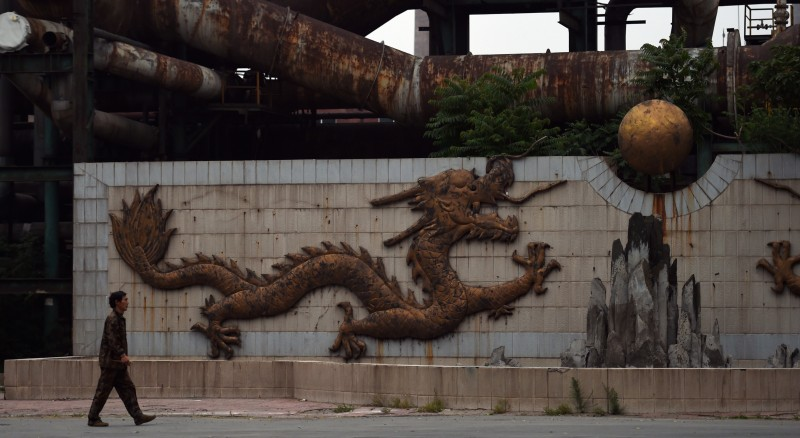 This photo taken on May 28, 2015 shows a worker walking past a sculpture of a dragon near rusting pipes at the Shougang Capital Iron and Steel plant in Beijing. Founded in 1919, Shougang was once the largest steel plant in China, with tens of thousands of workers. But the facility was identified as the Chinese capitals biggest polluter and began a gradual shutdown in 2005 as part of an effort to improve air quality ahead of the 2008 Olympics, finally producing its last steel in early 2011. Local officials have said the 8.6 square km (3.3 square mile) facility will be turned into an arts, tourism and finance hub, but progress has been slow and the decaying site is still reportedly blighted by soil pollution built up during the plants industrial heyday.  AFP PHOTO / GREG BAKER        (Photo credit should read GREG BAKER/AFP/Getty Images)