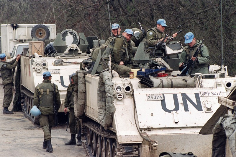 Canadian blue helmets check their weapons, 17 April 1993 near Tuzla's airport, waiting to depart for the Moslem enclave of Srebrenica, where some 30000 refugees hope to be evacuated from. (Photo credit should read PASCAL GUYOT/AFP/Getty Images)