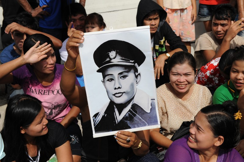 A supporter of Myanmar opposition leader Aung San Suu Kyi holds a portrait of her father and independence hero General Aung San ahead of her arrival at the Bangkok National Verification Centre in Samut Sakhon on the outskirts of Bangkok on May 31, 2012.    Suu Kyi is on her first trip abroad in 24 years by telling an ecstatic crowd of Myanmar migrants in Thailand she would do all she could to help them.  AFP PHOTO/Christophe ARCHAMBAULT        (Photo credit should read CHRISTOPHE ARCHAMBAULT/AFP/GettyImages)