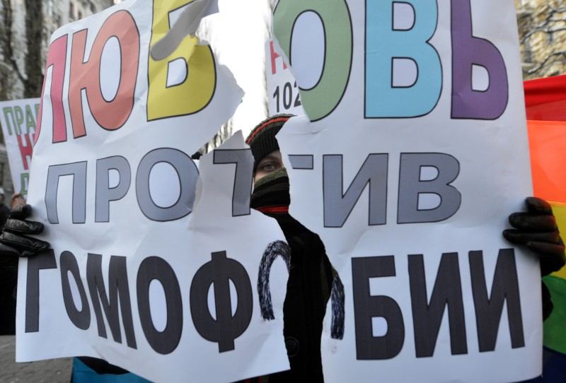 "An activisit of an Ukrainian human rights organization hold a placard reading ""Love is against homophobia"" during a rally marking an International Human Rights Day in the center of Kiev on December 8, 2012. A court prohibited human rights supporters to celebrate the Human Rights Day . AFP PHOTO/ SERGEI SUPINSKY              (Photo credit should read SERGEI SUPINSKY/AFP/Getty Images)"