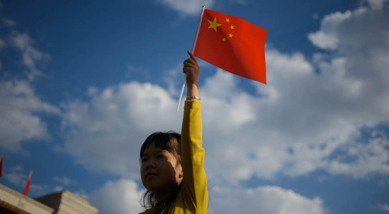 A girl waves a Chinese flag on Tiananmen Square in Beijing on October 1, 2013. China was celebrating its National Day, marking the 64th anniversary of the founding of the People's Republic of China by Mao Zedong. AFP PHOTO / Ed Jones        (Photo credit should read Ed Jones/AFP/Getty Images)