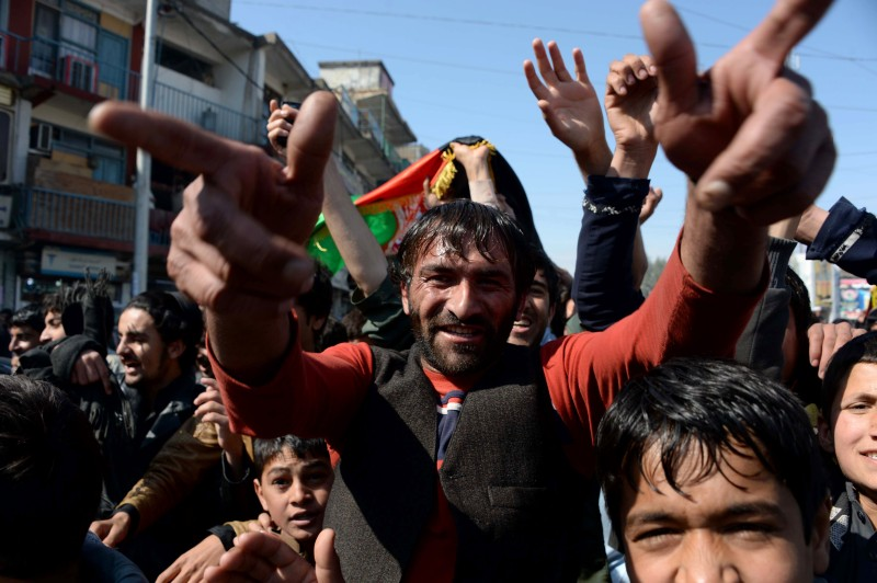 Afghan cricket fans celebrate their national cricket team victory in the World Cup 2015 match between Afghanistan and Scotland, in Jalalabad capital of Nangarhar province on February 26, 2015.   Hundreds of Afghan cricket fans poured onto the streets in southern Kandahar and eastern Jalalabad carrying Afghan flags, dancing in celebration and firing celebratory gunfire after their team registered their first famous World Cup win over Scotland.   AFP PHOTO / Noorullah SHIRZADA        (Photo credit should read Noorullah Shirzada/AFP/Getty Images)