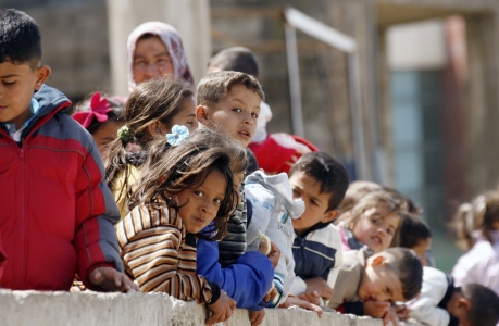 Children watch during a visit of French Junior Minister for Development and French-Speaking Communities minister at a camp housing Syrian refugees who fled Hama province on March 22, 2015 in the Lebanese southern city of Sidon. AFP PHOTO / MAHMOUD ZAYYAT (Photo credit should read MAHMOUD ZAYYAT/AFP/Getty Images)