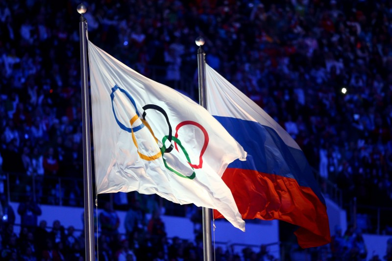 SOCHI, RUSSIA - FEBRUARY 23:  The Olympic flag and Russian flag are raised as the Russian National Anthem is sung during the 2014 Sochi Winter Olympics Closing Ceremony at Fisht Olympic Stadium on February 23, 2014 in Sochi, Russia.  (Photo by Paul Gilham/Getty Images)
