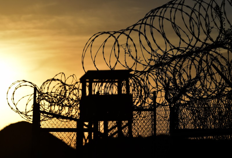 "This photo made during an escorted visit and reviewed by the US military, shows the razor wire-topped fence and a watch tower at the abandoned ""Camp X-Ray"" detention facility at the US Naval Station in Guantanamo Bay, Cuba, April 9, 2014.   AFP PHOTO/MLADEN ANTONOV        (Photo credit should read MLADEN ANTONOV/AFP/Getty Images)"
