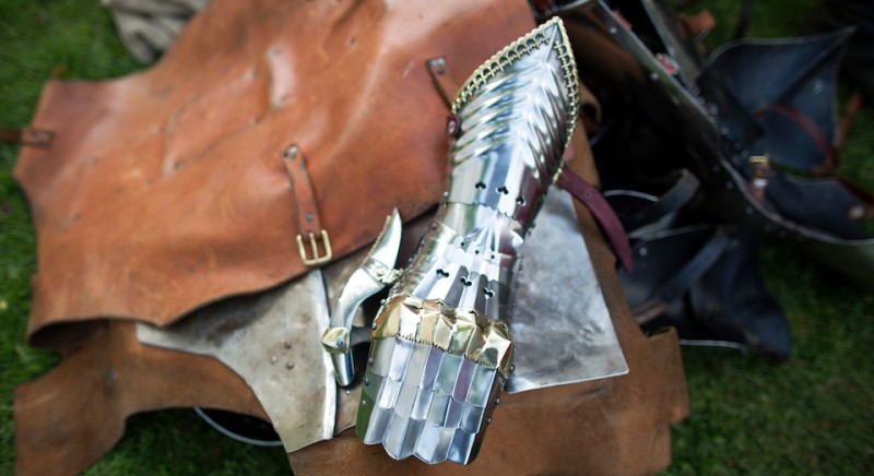 BEDFORD, ENGLAND - APRIL 26:  A re-enactor's armour is removed after a display on the first day of the 'St George's Festival' at the English Heritage's Wrest Park estate on April 26, 2014 near Bedford, England. 'St George's Festival' at Wrest Park takes place on April 26 and 27, 2014 and features reenactments of various eras of British history from medieval times to the First World War.  (Photo by Oli Scarff/Getty Images)