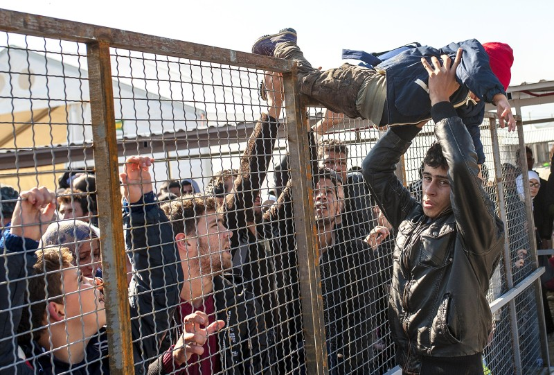 A child is passed over a fence as migrants and refugees prepare to board a train heading to Serbia from the Macedonian-Greek border near Gevgelija on October 25, 2015.  European Union and Balkan leaders hold emergency talks on Europe's refugee crisis amid threats from three frontline states to close their borders if northern EU countries stop accepting migrants. The mini summit, called by European Commission President Jean-Claude Juncker, groups the heads of 10 EU nations, including German Chancellor Angela Merkel, plus the leaders of Albania, Serbia and Macedonia.  AFP  PHOTO / ROBERT ATANASOVSKI        (Photo credit should read ROBERT ATANASOVSKI/AFP/Getty Images)