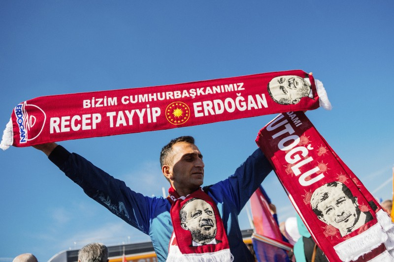 A street vendor sells scarves of Turkish President Recep Taqyyip Erdogan, as supporters wait for the Turkish Prime Minister Ahmet Davutoglu (unseen) at the Istanbul Ataturk airport on November 3, 2015 in Istanbul. Turkey's long dominant Justice and Development Party (AKP) scored a stunning election success at the weekend with a vote that returned it to single-party rule after months of political uncertainty. The result is likely to bolster strongman President Recep Tayyip Erdogan as he seeks to expand his powers, but analysts warn it could further exacerbate deep rifts in Turkish society. AFP PHOTO / OZAN KOSE        (Photo credit should read OZAN KOSE/AFP/Getty Images)