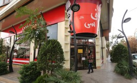 """A woman walks past the fried chicken shop """"KFC Halal"""", using the brand name of US fast food giant KFC, after it was closed by Iranian police, on November 3, 2015, in the capital Tehran. """"Police closed the 'KFC' restaurant as it didn't have authorisation and had been operating under a false license,"""" reported the news site of Iran's Young Journalist Club, which is affiliated with state television. AFP PHOTO / STR        (Photo credit should read -/AFP/Getty Images)"""