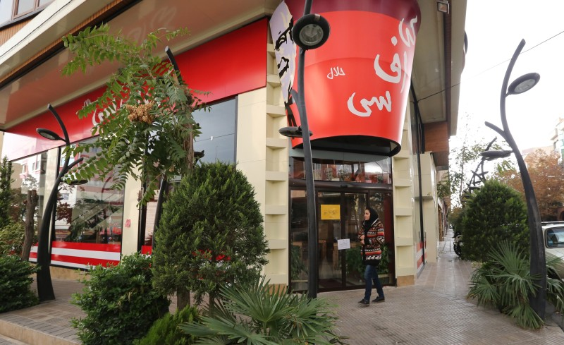 "A woman walks past the fried chicken shop ""KFC Halal"", using the brand name of US fast food giant KFC, after it was closed by Iranian police, on November 3, 2015, in the capital Tehran. ""Police closed the 'KFC' restaurant as it didn't have authorisation and had been operating under a false license,"" reported the news site of Iran's Young Journalist Club, which is affiliated with state television. AFP PHOTO / STR        (Photo credit should read -/AFP/Getty Images)"