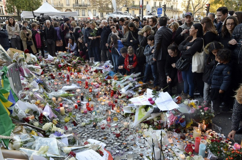 People gather at a makeshift memorial near the Bataclan concert hall in Paris on November 15, 2015, two days after a series of deadly attacks. Islamic State jihadists claimed a series of coordinated attacks by gunmen and suicide bombers in Paris on November 13 that killed at least 129 people in scenes of carnage at a concert hall, restaurants and the national stadium. AFP PHOTO / MIGUEL MEDINA        (Photo credit should read MIGUEL MEDINA/AFP/Getty Images)
