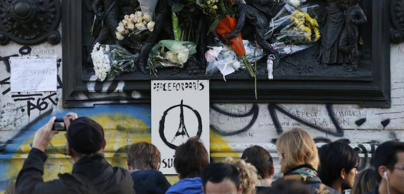 A sign reading 'Peace for Paris' is seen as people gather around the Monument a la Republique, at the Place de la Republique in Paris, on November 15, 2015, two days after a series of deadly attacks. Islamic State jihadists claimed a series of coordinated attacks by gunmen and suicide bombers in Paris on November 13 that killed at least 128 people in scenes of carnage at a concert hall, restaurants and the national stadium. AFP PHOTO / PATRICK KOVARIK        (Photo credit should read PATRICK KOVARIK/AFP/Getty Images)