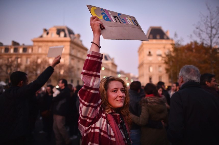 PARIS, FRANCE - NOVEMBER 15:  A woman holds a sign offering free hugs as people gather at Place de la Republique as France observes three days of national mourning for the victims of the terror attacks on November 15, 2015 in Paris, France. As France observes three days of national mourning members of the public continue to pay tribute to the victims of Friday's deadly attacks. A special service for the families of the victims and survivors is to be held at Paris's Notre Dame Cathedral.  (Photo by Jeff J Mitchell/Getty Images)