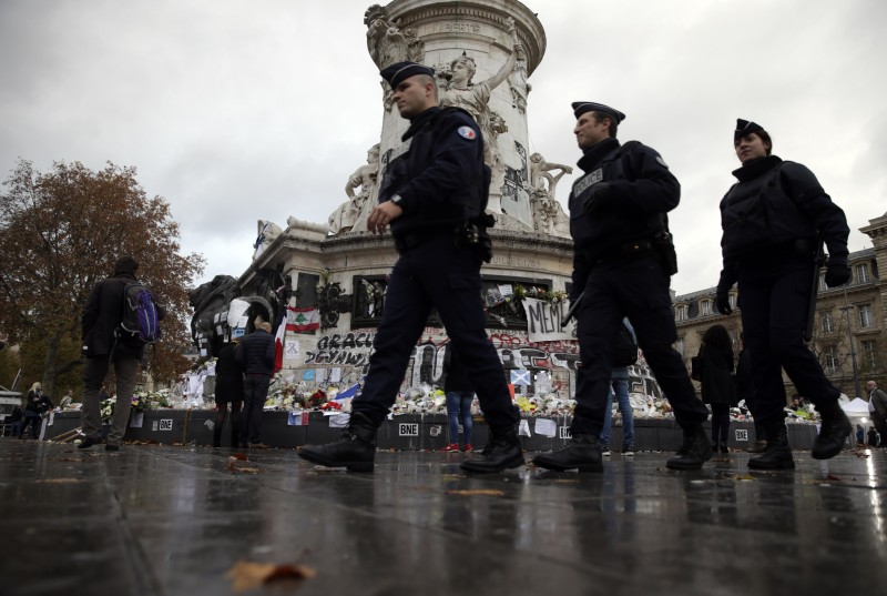 French policemen patrol next to the makeshift memorial made up with flowers, candles and messages, on November 17, 2015, at the Place de la Republique square in Paris, in tribute to the victims of the attacks claimed by Islamic State which killed at least 129 people and left more than 350 injured on November 13 in Paris. AFP PHOTO / KENZO TRIBOUILLARD        (Photo credit should read KENZO TRIBOUILLARD/AFP/Getty Images)