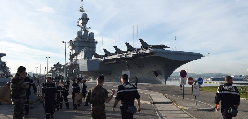 French naval sailors walk to the aircraft carrier Charles-de-Gaulle at a military port in the southern French city of Toulon, on November 18, 2015, before leaving in Eastern Mediterranean Sea. France said its Charles de Gaulle aircraft carrier would be deployed to the eastern Mediterranean to boost operations in Syria as Paris intensifies a bombing campaign against the Islamic State group there. The latest move follows attacks in the French capital, claimed by the jihadist group, which left 129 people dead and hundreds more wounded. AFP PHOTO / ANNE-CHRISTINE POUJOULAT        (Photo credit should read ANNE-CHRISTINE POUJOULAT/AFP/Getty Images)