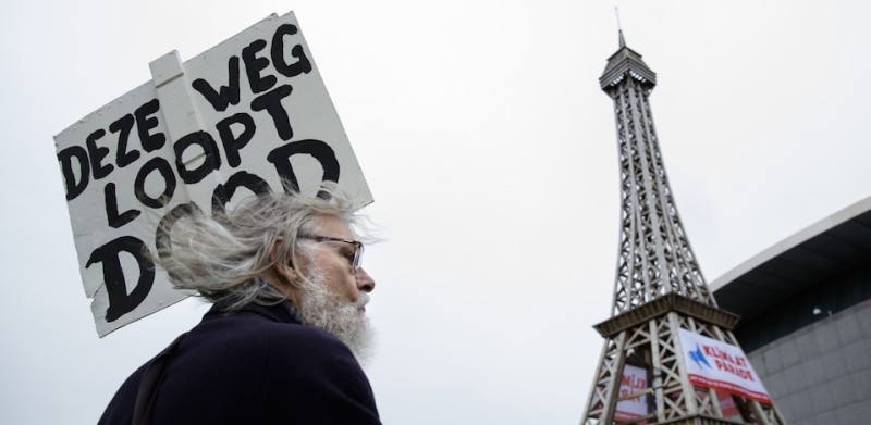 "A man holds a placard reading in Dutch ""Deze weg loopt dood"" which translates as ""This road is a dead end"" on November 29, 2015 during a Climate March in Amsterdam on the eve of the official opening of a 195-nation UN climate summit in Paris. More than 140 world leaders are gathering around Paris for high-stakes climate talks that start November 30, and activists are holding marches and protests around the world to urge them to reach a strong agreement to slow global warming. AFP PHOTO / ANP / BART MAAT  ==NETHERLANDS OUT==  / AFP / ANP / BART MAAT        (Photo credit should read BART MAAT/AFP/Getty Images)"