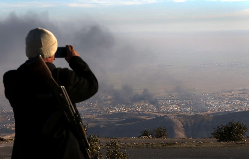 A displaced Iraqi man from the Yazidi community, who fled violence between Islamic State (IS) group jihadists and Peshmerga fighters in the Iraqi town of Sinjar, in the northern Iraqi province of Mosul, looks on as smoke billows during an operation by Iraqi Kurdish forces backed by US-led strikes in the northern Iraqi town of Sinjar on November 12, 2015, to retake the town from the Islamic State group and cut a key supply line to Syria. AFP PHOTO / SAFIN HAMED        (Photo credit should read SAFIN HAMED/AFP/Getty Images)