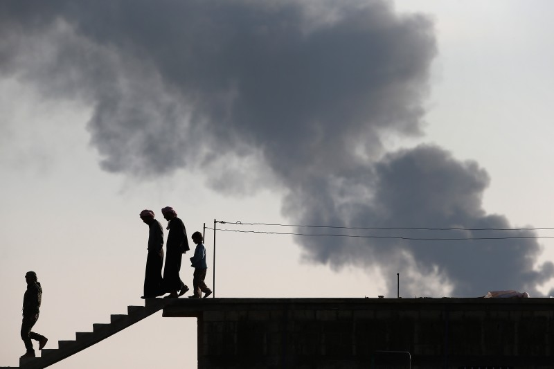 HOLE, SYRIA - NOVEMBER 10:  People walk from a rooftop overlooking a burning oil well on November 10, 2015 near the ISIL-held town of Hole in the autonomous region of Rojava, Syria. A coalition of forces, primarily Kurdish, are attacking ISIL extremists in the area near the Iraqi border and calling in airstrikes from U.S.-led coalition warplanes. The autonomous region of Rojava in northern Syria has become a bulwark against the Islamic State. The Rojava armed forces, with the aid of U.S. airstrikes and weapons, are retaking territory which had earlier been captured much by ISIL from the Syrian regime.  (Photo by John Moore/Getty Images)