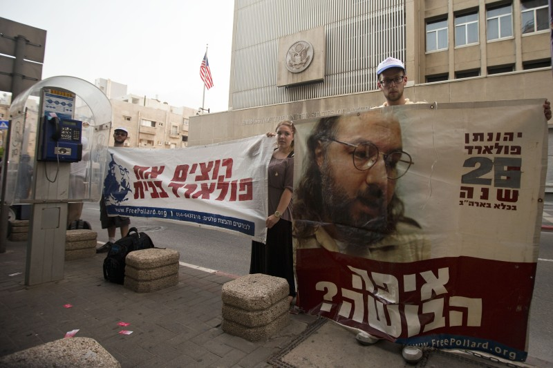 """Israeli protesters hold a slogan which reads in Hebrew """"We want Pollard back home"""" and """"Where is the shame?"""" during a protest in front of the US embassy in the Mediterranean coastal city of Tel Aviv on July 17, 2012 to call for the release of Jewish-American spy Jonathan Pollard. Pollard, who is jailed in the United States on charges of passing thousands of secret documents about American spy activities in the Arab world to Israel in the 1980s and was sentenced to life in prison by a US court in 1987. AFP PHOTO/JACK GUEZ        (Photo credit should read JACK GUEZ/AFP/GettyImages)"""