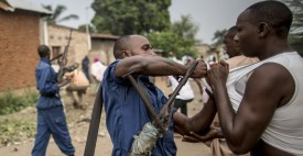 A man is detained by a Burundi policeman  during a scuffle with residents angered by a search operation in the of the Cibitoke neighbourhood of Bujumbura on June 27, 2015.  Burundi's ambassador to the United Nations said Friday that elections will go ahead as planned next week, despite the opposition vowing to boycott the polls and the US withdrawing its assistance. Parliamentary elections are set to be held on June 29, 2015 and a presidential vote on July 15, despite months of turmoil sparked by President Pierre Nkurunziza's bid for a third term in office.  AFP PHOTO/MARCO LONGARI        (Photo credit should read MARCO LONGARI/AFP/Getty Images)