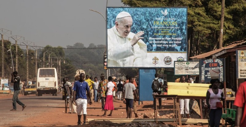 People walk by a billboard welcoming Pope Francis ahead of his visit in Bangui on November 25, 2015. Pope Francis on November 25 warned of the need to tackle poverty as a key driver of conflict and violence as he kicked off a landmark Africa trip fraught with security concerns. AFP PHOTO / GIANLUIGI GUERCIA / AFP / GIANLUIGI GUERCIA        (Photo credit should read GIANLUIGI GUERCIA/AFP/Getty Images)