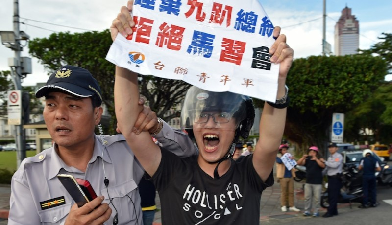 "A pro-independence activist displays a sign that reads ""black box (operation) for the Ma-Xi meeting"" while arrested by police for throwing a smoke bomb in front of the Presidential Palace in Taipei on November 4, 2015.  The presidents of China and Taiwan will meet this weekend in Singapore with a handshake that will mark a seismic shift in a relationship frozen in enmity since 1949.  AFP PHOTO / Sam Yeh        (Photo credit should read SAM YEH/AFP/Getty Images)"