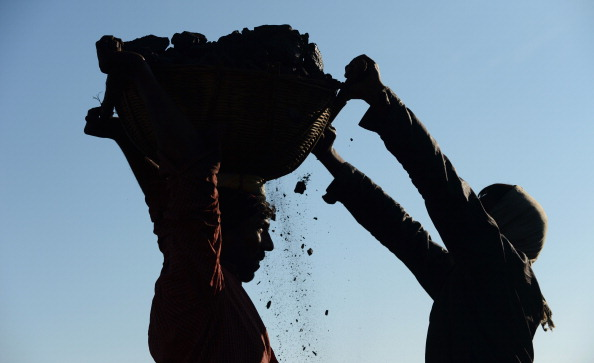 In this photograph taken on January 31, 2013, miners haul baskets full of coal as they load a truck with coal at a road side coal depot near Rymbai village in the Indian northeastern state of Meghalaya.  Thousands of private mines employ slim men and boys that will fit in thin holes branching out from deep shafts dug out from the ground in the East Jaintia Hills in Northeastern Indian state of Meghalaya. This state is the only state in India where coal mining is done privately by mine owners, who use cheap labour to supply the demand for this energy resource. Accidents and quiet burials are commonplace, with years of uncontrolled drilling making the rat-hole mines unstable and liable to collapse at any moment. After decades of unregulated mining, the state is due to enforce its first-ever mining policy later this year. AFP PHOTO/ Roberto Schmidt        (Photo credit should read ROBERTO SCHMIDT/AFP/Getty Images)