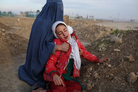 Najibah tried to comfort her daughter Zahra (8) as they both wept over the grave of their husband and father, just south of Kunduz City. Sub Caption: During the two week takeover of Kunduz City by the Taliban from September 28 - October 12, 43-year-old Baynazar Mohammad Nazar (***First name only to be used because of potential threats to his family***) was shot in crossfire between government forces and Taliban fighters on his way home from where he works as a Chowkidor (unarmed guard) in Kunduz City. He spent the next two and a half days being operated on and recovering in the nearby MSF Kunduz Trauma Center. At around 2AM on Saturday, October 3, however, Baynazar was one of at least thirty patients, patient carers and staff who were killed when a U.S. AC-130 gunship destroyed much of the hospital after receiving a request for air support from Afghan Commandos in the area. Baynazar's family spent ten days searching for him - from Kunduz to Baghlan Province to Mazar-e Sharif and back to Kunduz, eventually being told by a shopkeeper near the hospital that he and 12 others had been taken from the hospital and buried on the edge of the city. He is survived by his wife, Najibah, sons, Samiullah (19) and Mohammad Khalid (6) and daughters Raiana (10) and Zahra (8).